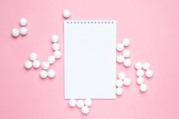 Бизнес блокнот и белые пластиковые шарики на розовом Premium Фотографии