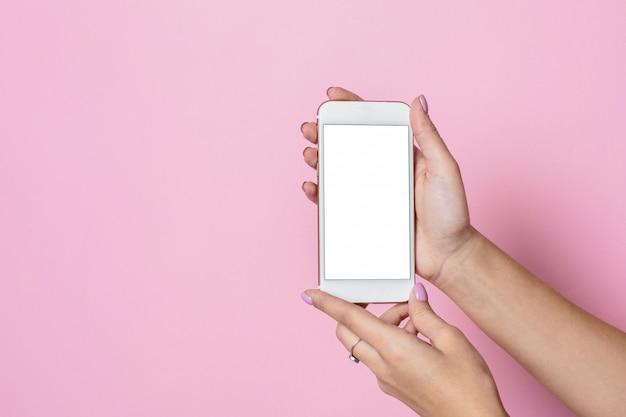 Женские руки держат мобильный телефон с белым экраном на розовой поверхности Premium Фотографии