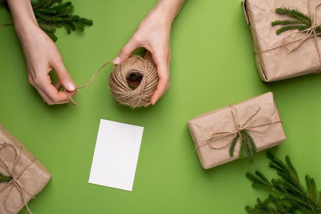 手のエコひもと緑の表面にペーパークラフトの緑の植物との贈り物 Premium写真