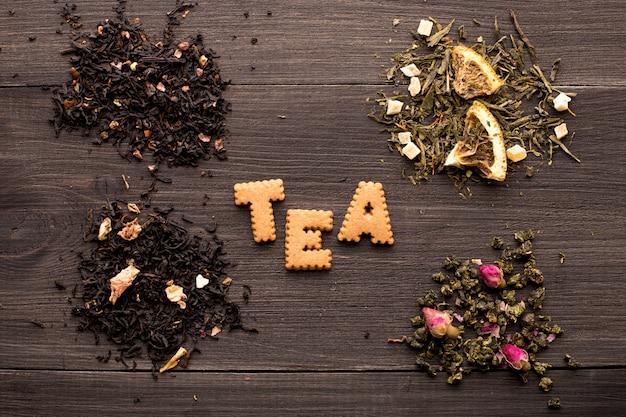 木製のテーブルに紅茶とクッキーの碑文のいくつかのビュー Premium写真