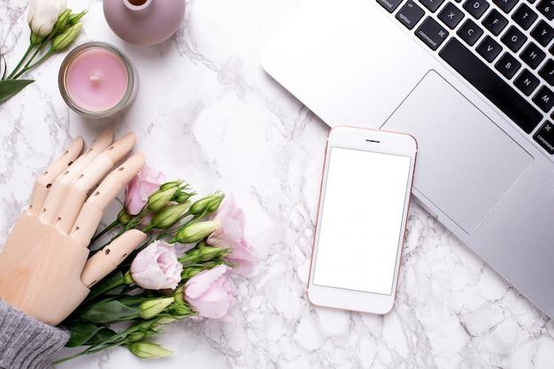 携帯電話と大理石のピンクの花を持つ木製の手 Premium写真