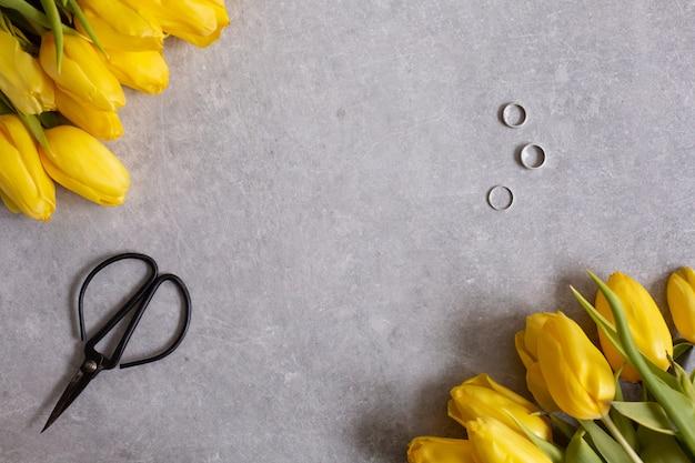 黄色の花チューリップとはさみのトップビュー Premium写真