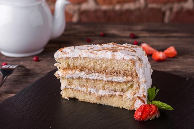 Бисквитный торт с кремом и карамелью на каменной плите на деревенском деревянном столе Premium Фотографии