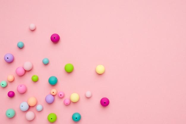 ピンクの背景。カラフルなパステルビーズ。ガーリーなミニマリストの構成 Premium写真