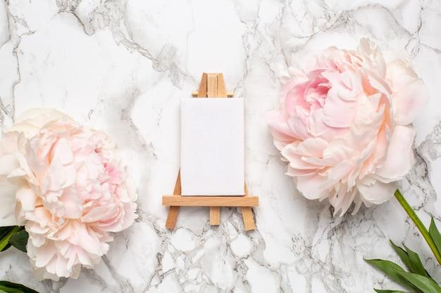 大理石の表面にキャンバスとピンクの牡丹の花を塗る小さなイーゼル。 Premium写真