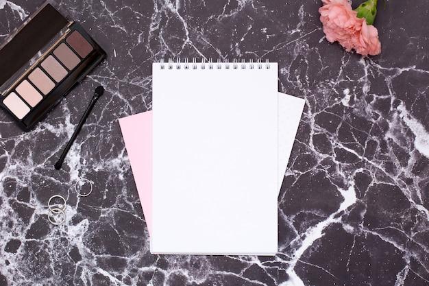 黒い大理石のテーブルに女性用ノートと化粧品 Premium写真