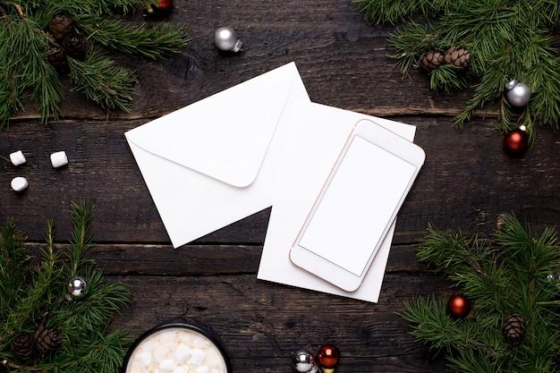 携帯電話とはがきクリスマスツリーと木製のテーブル Premium写真