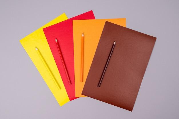 灰色の色紙と黄色、赤、オレンジと茶色の鉛筆 Premium写真
