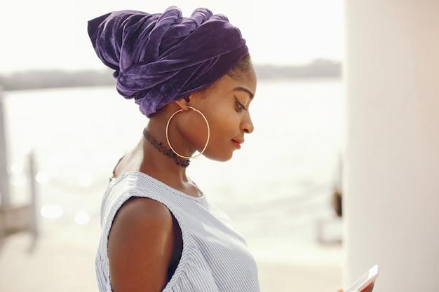 美しくてスタイリッシュな暗い肌の女の子が晴れた夏の街を歩く 無料写真