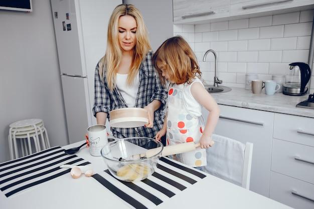 彼女の小さな娘と美しい若い母親は家庭の台所で料理しています 無料写真