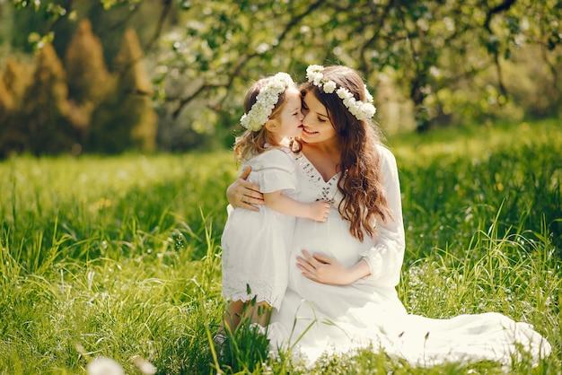小さな女の子と遊んで長い白いドレスで美しい若い妊娠中の女の子 無料写真