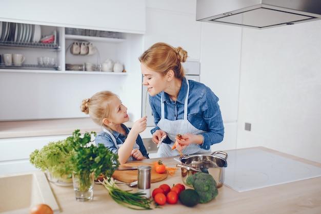ブルーシャツとエプロンの美しい母は、自宅で新鮮な野菜サラダを準備しています 無料写真