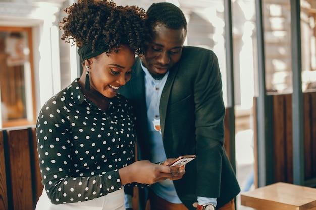 若い、スタイリッシュな暗い肌のカップルは、日当たりの良い都市に立っている 無料写真