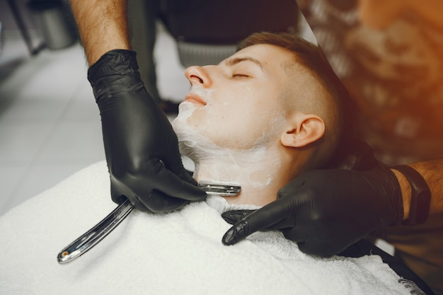 男は理髪店で彼のひげを切る。 無料写真