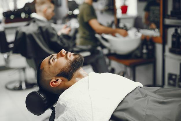 Человек режет бороду в парикмахерской. Бесплатные Фотографии