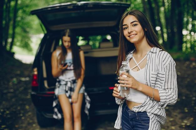 車の近くの二人の女の子 無料写真
