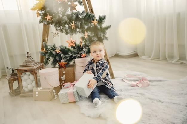 かわいい家族のクリスマスツリーのそばに座って 無料写真