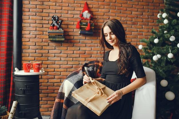 クリスマスの部屋に座っている美しい女の子 無料写真