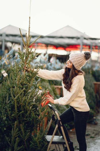 クリスマスツリーと白いセーターのかわいいブルネット 無料写真
