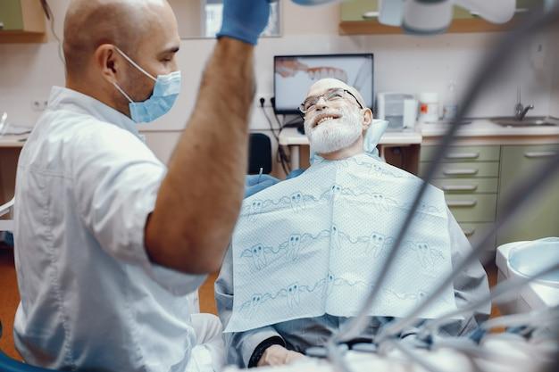 歯科医のオフィスに座っている老人 無料写真