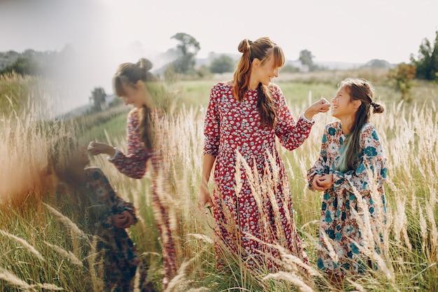 Милая и стильная семья на летнем поле Бесплатные Фотографии