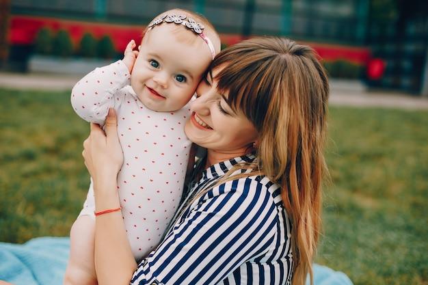 夏の公園で遊ぶ娘を持つ母 無料写真