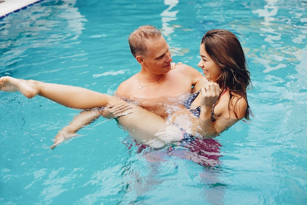 エレガントなカップルはプールで泳ぐ 無料写真