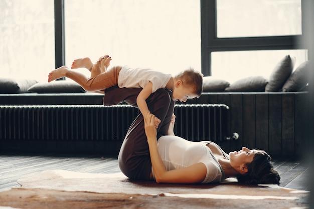 Мать с маленьким сыном занимаются йогой дома Бесплатные Фотографии