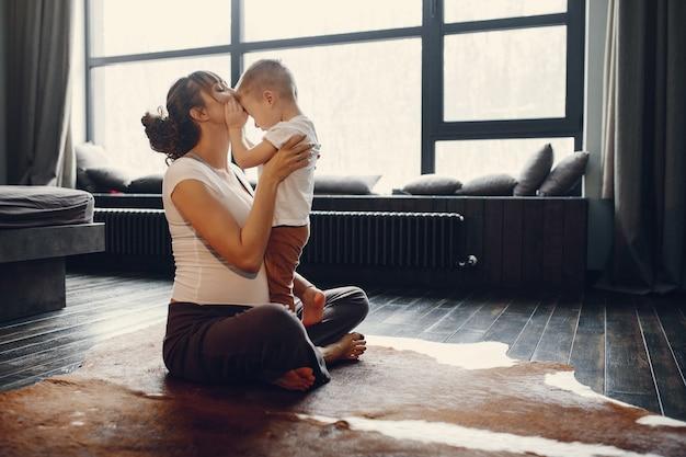 家でヨガをやっている幼い息子を持つ母 無料写真