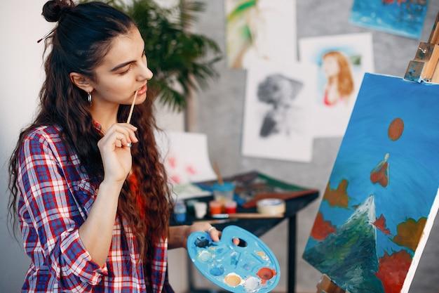 エレガントな女の子がアートスタジオで描く 無料写真
