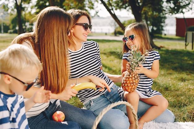 夏の公園で遊ぶ子供たちと母親 無料写真