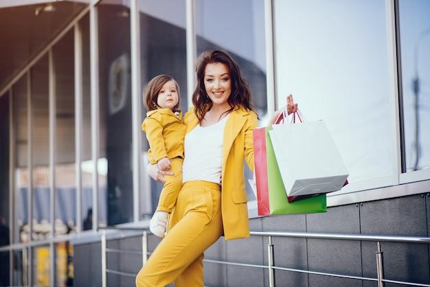 街で買い物袋を持つ母と娘 無料写真