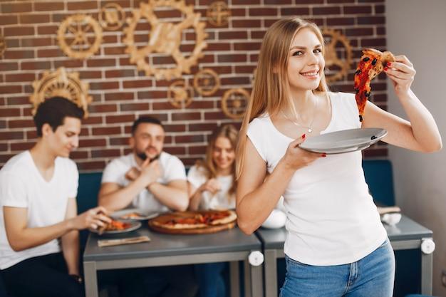 Милые друзья в кафе, едят пиццу Бесплатные Фотографии