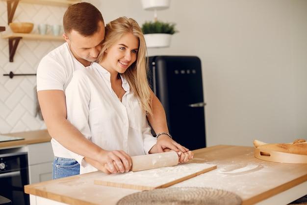 美しいカップルは台所で食べ物を準備します 無料写真