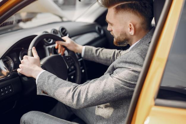 車のサロンでハンサムでエレガントな男 無料写真