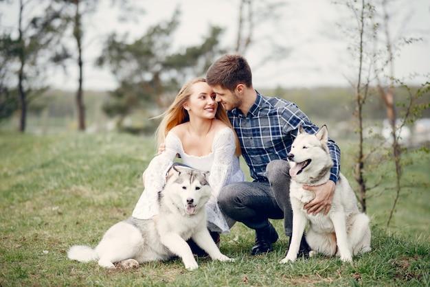 犬と夏の森の中の美しいカップル 無料写真