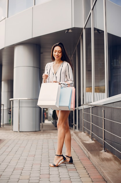 街で買い物袋を持つかわいい女の子 無料写真
