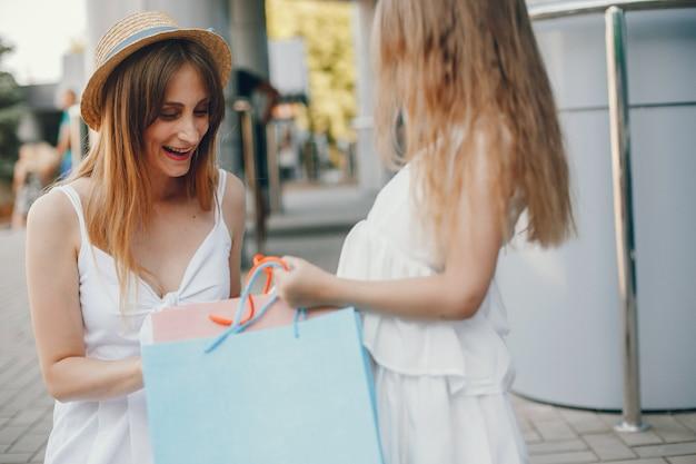 Мать и дочь с хозяйственной сумкой в городе Бесплатные Фотографии