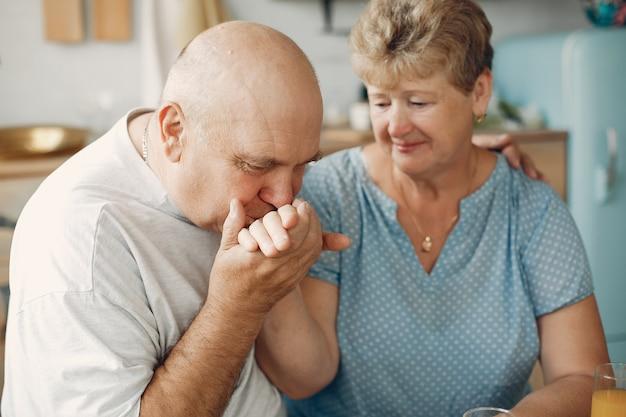 美しい老夫婦は、キッチンで食事を準備します 無料写真