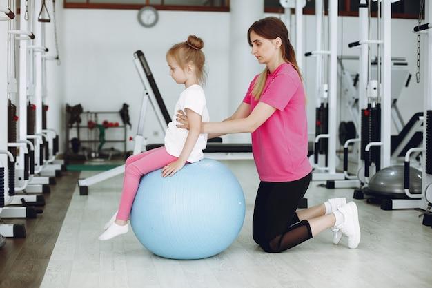 小さな娘を持つ母は、ジムで体操に取り組んでいます 無料写真