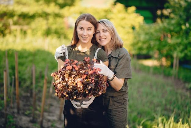 Мама с дочкой работает в саду возле дома Бесплатные Фотографии