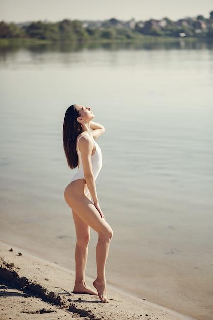 湖の近くのビーチで美しく、エレガントな女の子 無料写真