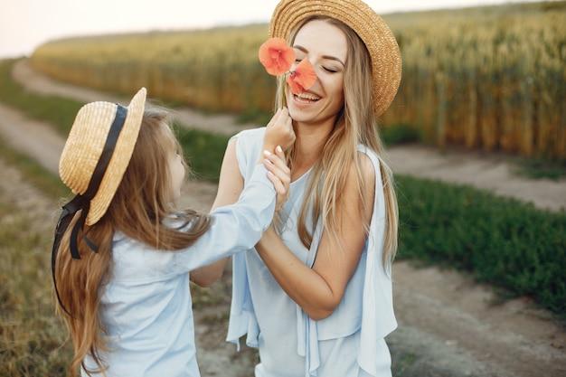 夏の畑で遊ぶ娘を持つ母 無料写真