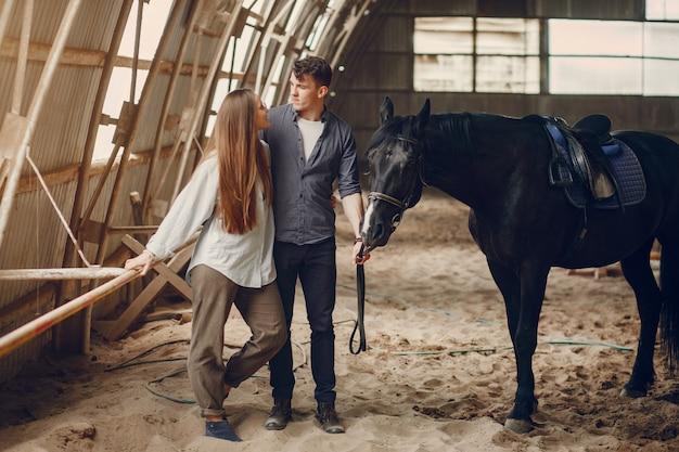 牧場で馬とかわいい愛情のあるカップル 無料写真