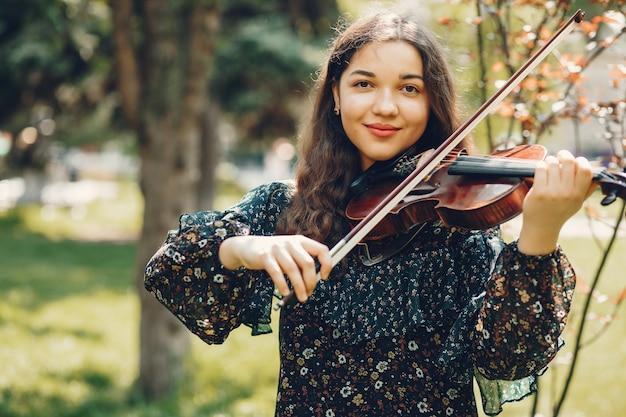 ヴァイオリンと夏の公園で美しい少女 無料写真