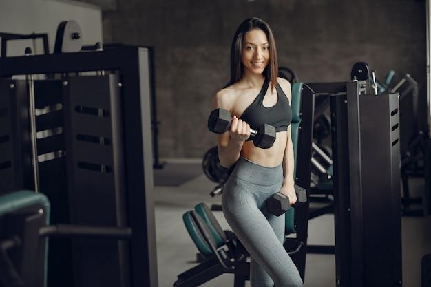 Красивая девушка занимается в тренажерном зале Бесплатные Фотографии