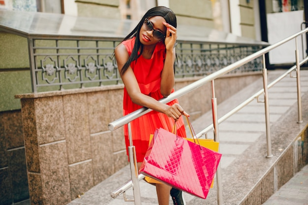 都市の買い物袋を持つ美しい黒の少女 無料写真
