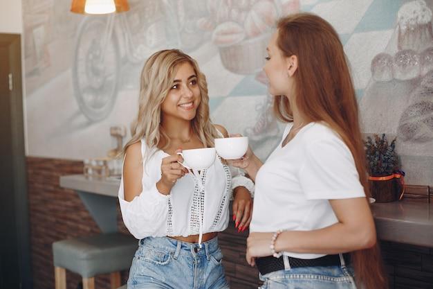 Модные молодые девушки сидят в кафе Бесплатные Фотографии