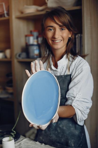 Молодая женщина делает керамику в мастерской Бесплатные Фотографии