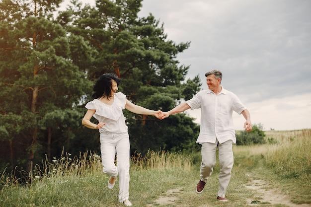 Красивая пара взрослых проводит время в летнем поле Бесплатные Фотографии